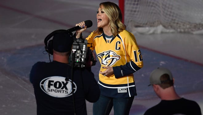 Carrie Underwood, wife of Nashville Predator Mike Fisher, sings the national anthem before the start of Game 3 in the first-round NHL playoff series at Bridgestone Arena on April 17, 2017.