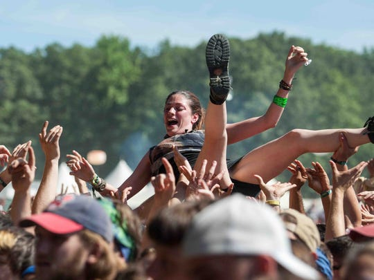 A fan crowd surfs as Weezer performs at the Firefly Music Festival in June.