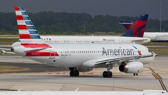 Surrounded by Delta Air Lines jets, an American Airlines