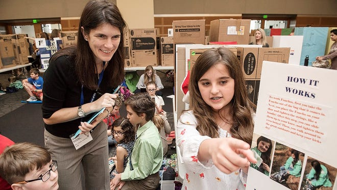 "Trisha Ambrose of Accenture Inc., left, a guest judge at MTSU's 26th annual Invention Convention, listens to  Dr. William Burrus Elementary School fifth-grader Grace Woods discuss her invention, ""Fonchos,"" which ""makes life easier"" by protecting shoes and pants from weather."