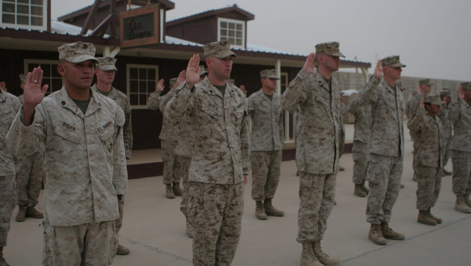 Marines raise their right hand during a mass reenlistment