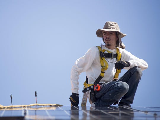 Joe Segundo installs solar panels on a house in Buckeye.