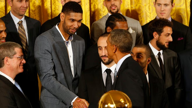 Tim Duncan shakes hands with President Barack Obama during a ceremony honoring the NBA Champion Spurs in the East Room at The White House.