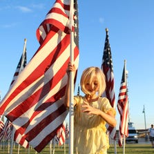 Taylor Burke inserts a flag into an iron stick. Burke is one of the volunteers who helped set up the Tempe Healing Fields in the Town Lake, in Tempe, Ariz., Wednesday, September 10, 2014. The Healing Fields stood for four days at the lake and brought thousands of visitors.
