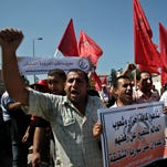 Palestinians supporters of the Popular Front for the Liberation of Palestine (PFLP), wave their red banners while chanting anti-American slogans during a protest against a possible military attack by the United States on Syria, in front of the United Nations Special Coordinator for the Middle East Peace Process offices in Gaza City, Tuesday, Sept. 10, 2013.