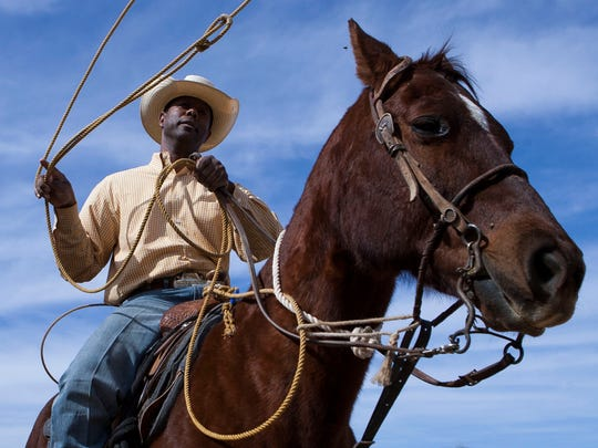 Robert Wooten practices with a lasso at his north Phoenix home. Wooten is training for the Arizona Black Rodeo.