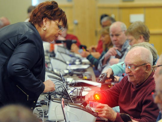Bev Chase, executive assistant for Sioux Falls Sioux District, assists Jim Page during Electronic Poll Book training for election workers at the Instructional Planning Center on Tuesday, April 7, 2015.