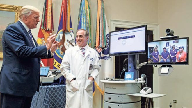 """Veterans Affairs Secretary David Shulkin watches as President Donald Trump talks with a patient to demonstrate """"telehealth"""" technology Thursday at the White House."""