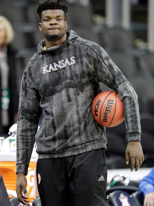 Injured Kansas center Udoka Azubuike watches while his team practices for an NCAA college basketball game in the Big 12 basketball tournament in Kansas City, Mo., Wednesday, March 7, 2018. Azubuike will miss the Big 12 tournament. (AP Photo/Orlin Wagner)