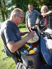 Brian Marek signs a paddle for Eric and Daniel Phendler as they prepare to leave the Rotary Park landing Monday, July 16, on the Mississippi River in Sartell.