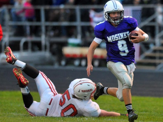 Mosinee quarterback Landon Stephan, right, runs the ball while Medford's Brett Paul makes a diving attempt at a tackle in a Great Northern Conference game Friday in Mosinee.