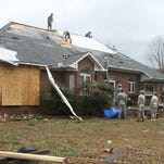 Friends and neighbors work on the roof of the home of Debbie McCormick on Shelby Road near Newton, Miss., that received extensive damage after a storm Tuesday, Feb. 2, 2016. A tornado damaged homes and at least one church, and strong winds damaged student housing at a community college Tuesday in eastern Mississippi. Authorities said no injuries were immediately reported.