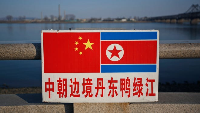 The Chinese and North Korean national flags are seen on a sign along the Yalu River where across is the North Korean town of Sinuiju in Dandong, Liaoning Province, China, April 7,  2013 (reissued Sept. 29, 2017).