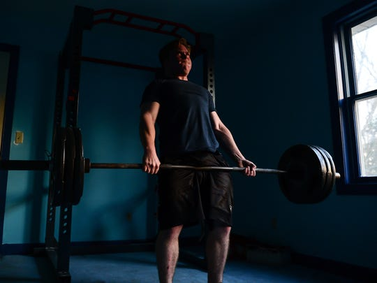 Skyler Hudson, 19, demonstrates powerlifting at his home.