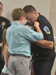 The daughter and son of newly-promoted Lt. Jonathan Young place a pin onto his uniform during a swearing-in and promotion ceremony at the Burlington Police Department on Thursday.