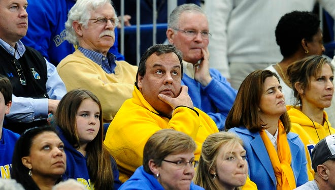 New Jersey Gov. Chris Christie, center, watches the first half of a game between Delaware and Kentucky in the NCAA college basketball tournament in 2013.