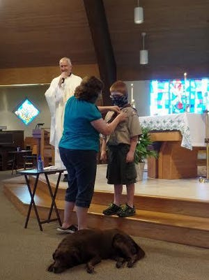 "The Rev. David Durkee, pastor of Queen of Heaven Catholic Church,celebrated his 40th ordination anniversary, which included recognition of Cub Scout Caleb Mancine. Durkee's dog, Sailor,""is in the foreground."