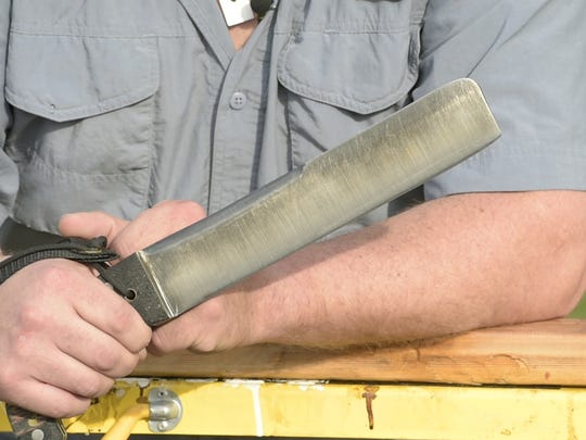 "Dwayne Unger holds up ""Black Mamba,"" a knife made from CPM M4 steel that features a 10-inch blade and weighs 2 pounds, 5 ounces. Unger gave the knife its nickname because of its especially dark tint."