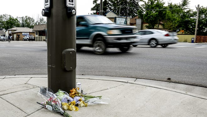 Cars pass a memorial set up in honor of William Connole Thursday, June 4, 2015, in Loveland, CO. The memorial is set up on the corner of St. Louis Ave. and East 1st Street near where he was shot and killed Wednesday night.