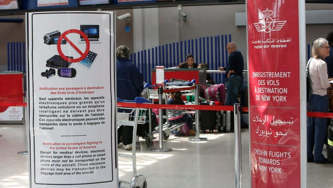 Placards inform passengers at the entrance to the Casablanca - New York flight checkpoint at Casablanca Mohammed V International Airport on March 29, 2017. The U.S. and British governments, citing unspecified threats, are barring passengers on some international flights from mostly Middle Eastern and North African countries from bringing laptops, tablets, electronic games and other devices on board in carry-on bags.