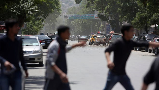 Afghans run from the site of a suicide attack, in the center of Kabul, on May 9.