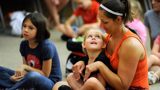 Leah Shaner, 4, looks up at he mother, Melissa, as they act out a story about a bunny rabbit being told by storyteller Bernadette Nason during the Young Audiences performance on Tuesday, June 13, 2017, at the Abilene Public Library's main branch.