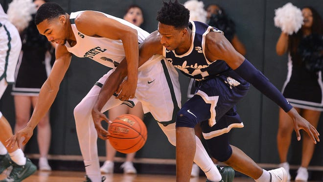 USC Upstate's Everette Hammond (2) battles for the ball with Charleston Southern's Phlandrous Fleming Jr. (24) during a Big South Conference game.