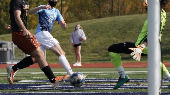 Siena Heights midfielder Remy Collard (20) scores a goal past Lourdes (Ohio) defender Brendon Long, left, and goalkeeper Ali Chokr during the first half of the Saints' 2-1 victory on Saturday at O'Laughlin Stadium.