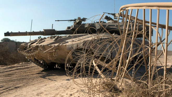 An Israeli tank stops at a gate inside southern Israel at an unspecified location on the border with the Gaza Strip on Aug. 21, 2014.