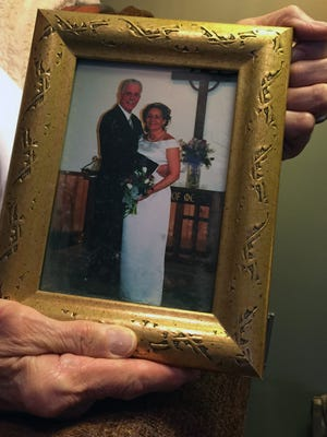 Ross Gibson displays a photo from his wedding day, 13 years ago. He and his wife Debra are both employees of the Michigan Department of Corrections.