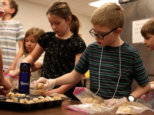 Thomas Wright places pieces of sugar coated bread into a cupcake pan during STEAM Spring Break Camp March 14, 2017, at San Angelo Museum of Fine Arts.