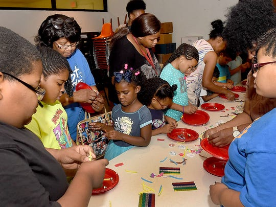 Children and their parents and grandparents enjoy arts and craft day at the Opelousas Public Library.