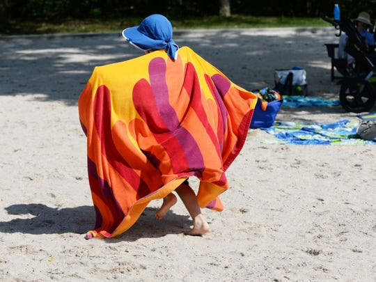 Baht Choe runs on the sand draped in a towel at Graydon pool in Ridgewood on Saturday August 05, 2017.