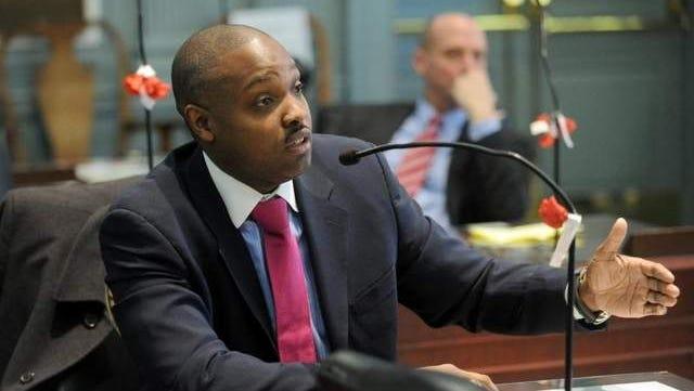 State Treasurer Chip Flowers Jr. during a house administration committee hearing at Legislative Hall . Listening in background to Flowers' testimony is Secretary of State Jeffrey W. Bullock.
