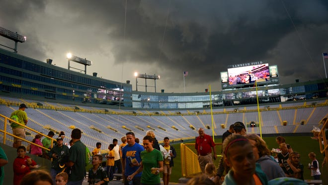 """Moviegoers evacuate the stands at Lambeau Field as a storm delays the showing of """"Wreck-It-Ralph'' on July 26. H. Marc Larson/Press-Gazette Media"""