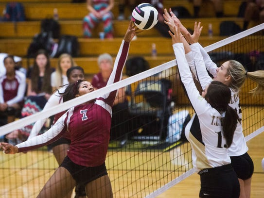 Westside's Asha Robinson spikes the ball but is blocked