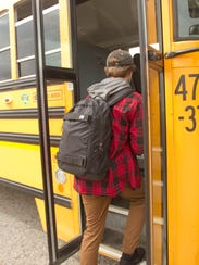 A student boards the bus from Highlander Way Middle