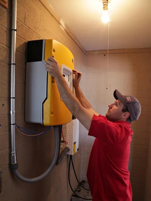 Mike Reilly, of American Solar and Roofing installs the cover to a solar power inverter/ charger on Tuesday in the Phoenix home of his boss, Joy Seitz, who is the president and CEO of American Solar & Roofing.