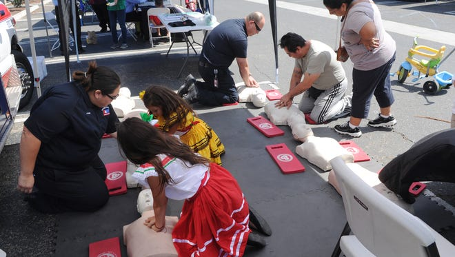 Alexandria Palma, left, American Medical Response, gives CPR demonstrations as the Oxnard Fire Department hosts a Disaster Preparedness Fair earlier this month. A variety of displays and hands-on practice allowed people to learn how to prepare for natural disasters.