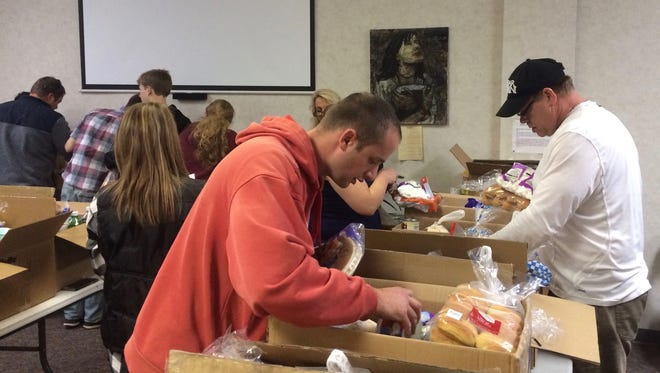 """""""I'm not very good at counting, so I like to see the smile when I hand them the box,"""" said Josiah Potter, of Redeeming Life Ministries, as he does a final box check along with other members of his church as they prepare for delivery of the Thanksgiving donations on Monday, Nov. 21, 2016 in Staunton, Va."""