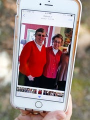 Jamie Sample, a parishioner of St. Thomas the Apostle Catholic Church in Lexington, Miss., sits in the shade in Durant, Miss., and shows a smartphone photograph taken last December 2015, of Sisters Paula Merrill, left, and Margaret Held. The two nuns who worked as nurses, and lived in Durant, Miss., were found slain in their home Thursday, Aug. 25, 2016. There were signs of a break-in and their vehicle was missing.