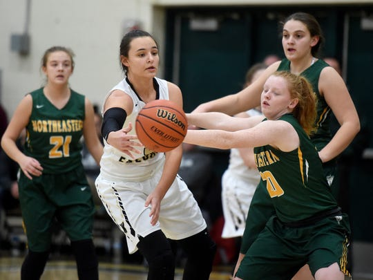Winchester's Maddie Lawrence passes the ball around Northeastern's Madi Clay and Tatum Jordan Saturday, Feb. 4, 2017, during the girls basketball sectional championship in Fountain City.