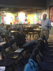"""Tony Redington, at right, on Tuesday discusses the merits of a """"mini-roundabout"""" at Howard and St. Paul Street with other Burlington residents at a gathering at ArtsRiot. Photographed June 27, 2017."""