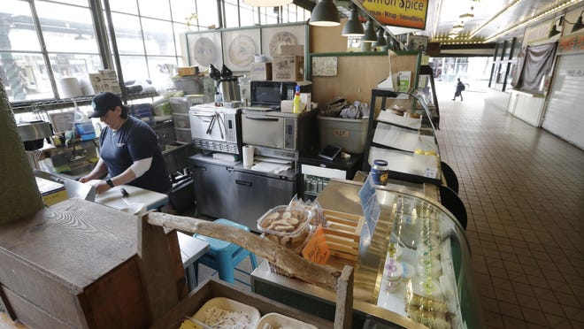 Bagel shop manager Samantha Maddocks runs the one shop still open in one walkway April 2 in the Pike Place Market in Seattle. Growth in the U.S. service sector slowed in March with a much bigger decline expected in coming months from all the shutdowns and job layoffs t