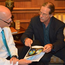 FSU professor Jeff Chanton shows Gov. Rick Scott some earth maps Tuesday during a meeting of the governor and five climate scientists.
