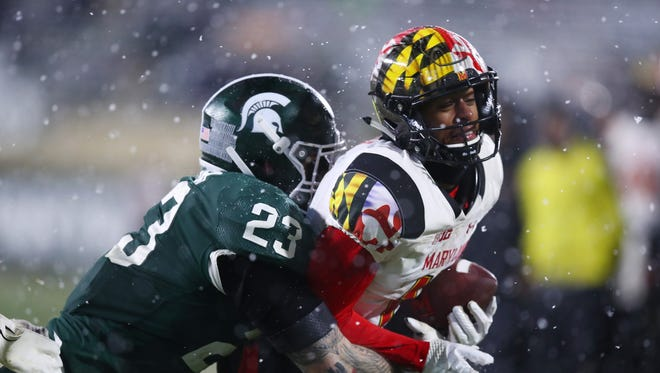 Taivon Jacobs of the Maryland Terrapins looks for yards after a second half catch while being tackled by Chris Frey of the Michigan State Spartans.