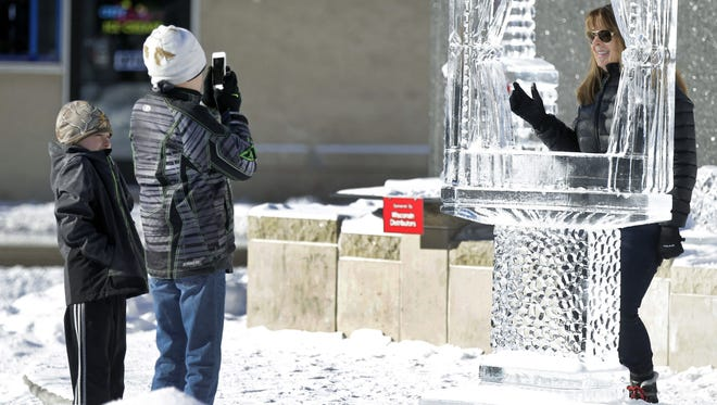 Kaden, left, and Brody Hillman of New London take a photo of their grandmother, Jo Hillman, while viewing ice sculptures Sunday at Houdini Plaza in Appleton.