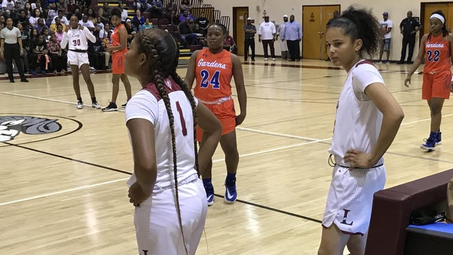 Palm Beach Lakes senior point guard Keishmy Ayuso, right, waits to check into the game early in the second quarter Tuesday night. Ayuso suffered an ankle injury in the first quarter but returned minutes later for the Rams, who hosted Palm Beach Gardens in the Class 7A Region 3 semifinal.