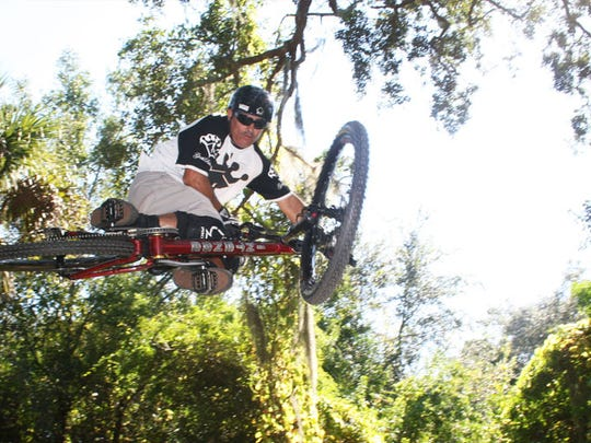 "Glen ""Vader"" Hawks hits one of the jump sections at the Grapefruit Trails in Palm Bay."