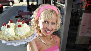 Linda Hundt shows just some of the award-winning baked goods at Sweetie-licious Bakery Cafe in DeWitt, in 2012.